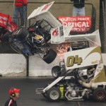 Ben Quinones' car goes flying into the backstretch fence – near a photographers stand – during the first heat race for winged outlaw modified midgets Friday in the Rumble in Fort Wayne. There were no injuries.  Kevin Lillard Photo
