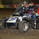 Justin Hendricks jumps the berm avoiding a wreck during Night #1 of the 2013 Chili Bowl Midget Nationals.  (Serena Dalhamer photo)
