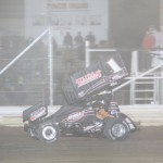 Nate Dussel takes the checker flag for the 305 sprint feature win. - Action Photo
