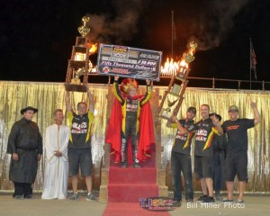 Brad Sweet hoists the $50,000 check while his team holds the trophies after winning the 2013 edition of the Kings Royal. - Bill Miller Photo