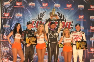 Bryan Clauson lifts the golden driller in victory lane after winning the Chili Bowl Nationals.  second place Kevin Swindell and second place and third place Christopher Bell also on the podium. - James McDonald / Apexone photo