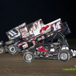Randy Hannagan (#11n), Brandon Wimmer (#24H), and Dale Blaney (#14K) racing three wide for position at Attica Raceway Park. - Mike Campbell Photo