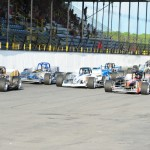A pack of Novelis Supermodifieds fly down the front stretch at the 'Steel Palace' during qualifying for the 2014 Jim Shampine Memorial 75. (Bill Taylor Photo)