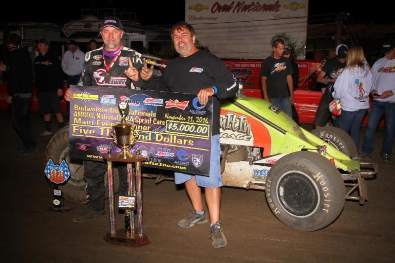 "Dave Darland (left) and car owner Jeff Walker celebrate in victory lane after winning Friday's night #2 of the ""Oval Nationals"" at Perris (Calif.) Auto Speedway. (Rich Forman Photo)"
