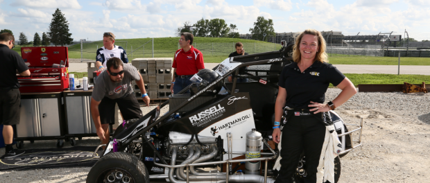 Sarah Fisher posing with her car at the Indianapolis Motor Speedway for the dirt oval exhibition with Tony Stewart. (Chris Jones/IMS Image)